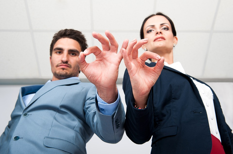 Man and woman on suit doing the OK sign to indicate a high-quality decision-making process